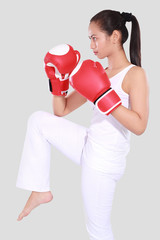 beautiful woman with the red boxing gloves, isolated on grey background