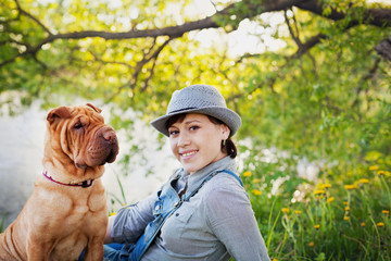 happy young woman in denim overalls and hat with red cute dog Shar Pei sitting in the field near the lake at sunset, true friends forever, people concept