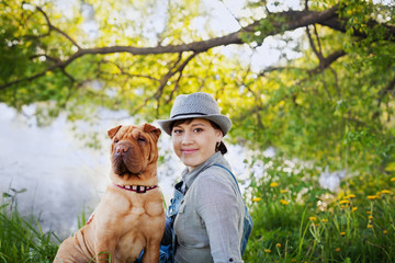 happy young woman in a hat with dog Shar Pei sitting in the field in sunset light, true friends forever, people concept