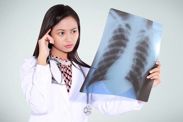 female doctor thinking and reading x-ray, isolated on green background