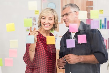 Business team pointing post its on the wall