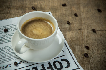 White cup of Espresso with Newspaper on the wooden table in the