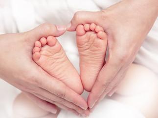 Baby's foot in mother hands closeup