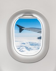Looking out the window of a plane to the aircraft wing and cloud