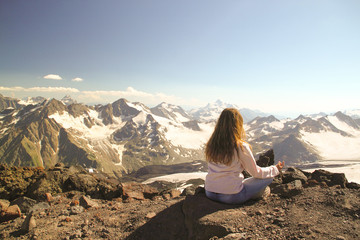 Thoughtful girl sitting on top of a mountain during a camping tr