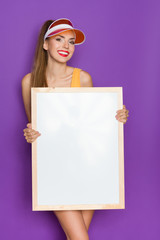 Smiling young woman in orange sun visor holding empty placard with wooden frame. Three quarter length studio shot on violet background.