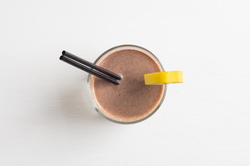 Glass of chocolate milkshake on the table