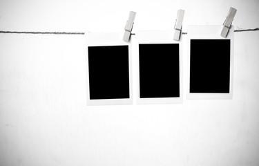Blank polaroid frames hanging over white background
