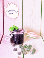 Blackberry jam with basil leaf on the old wooden table, toned vanilla picture, selective focus