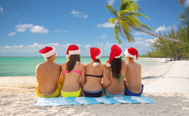 group of friends in santa helper hats on beach