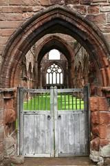 Vecchio accesso principale ad una abbazia diroccata con un tappeto verde al posto del pavimento