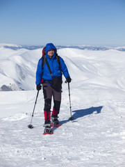 A man with a backpack and snowshoes.