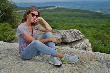 Young woman sitting at the edge of roc at Minnewaska State Park Reserve Upstate NY during summer time