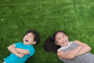 Cute asian child lying on green grass