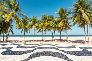 Palm trees and the iconic Copacabana beach mosaic sidewalk, in Rio de Janeiro, Brazil.