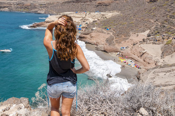 Girl looking at the wild beach in Tenerife