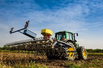 Bauer mit Traktor beim Säen und Auflockern des Bodens