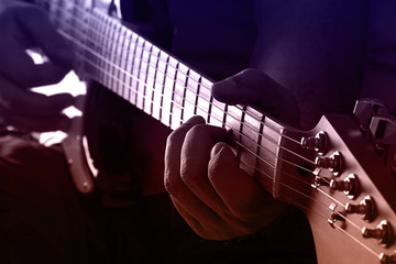 Playing guitar on purple and orange light