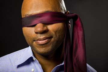 Black businessman blindfolded to represent corporate uncertainty