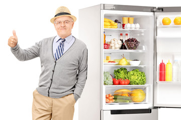 Senior leaning on a fridge and giving thumb up