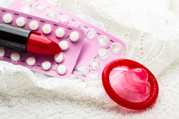 Pills condom and lipstick on lace lingerie.