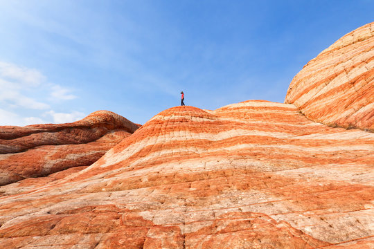 Female Hiker on top of the striped hill in Yant Flat located in Southern Utah.