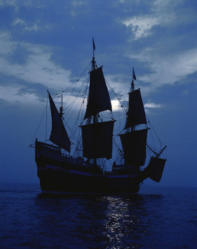 This is a replica of the ship Mayflower II. It demonstrates the first sailing in 1620 when the Pilgrims sailed to the New World. The ship shows full sails on a shimmering moonlit ocean against a dark blue night sky.