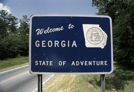 This is a road sign that says, welcome to Georgia, state of adventure. There is a white map of the state of Georgia on its right. There are green bushes on the sign's right and left.