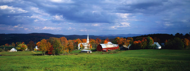 Wall Mural - This is a view of the village in autumn. There is a typical New England white church with a tall steeple and a red barn. There is a vast green field in front of the view of the village with fall foliage in the village.
