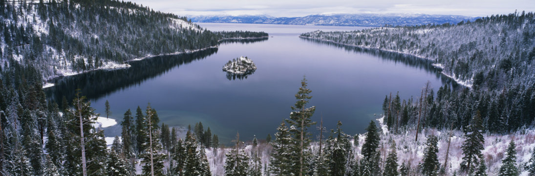 This is Emerald Bay after a winter snow storm. There is snow covering the ground surrounding the bay.