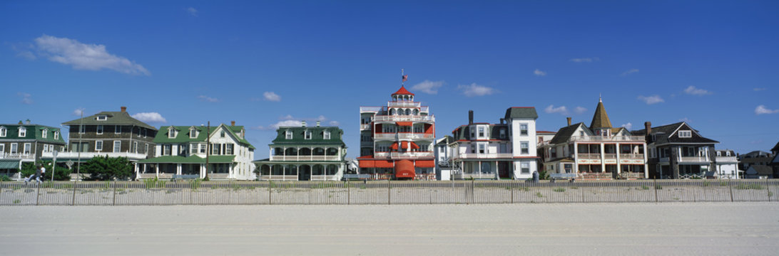 These are Victorian style homes overlooking the beach in Cape May. There is wooden fence separating the beach and the houses. The homes have large front porches. The sky is a deep blue with just a few white puffy clouds.