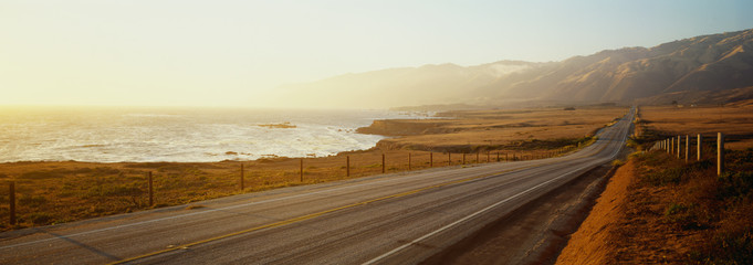 Poster Coast This is Route 1also known as the Pacific Coast Highway. The road is situated next to the ocean with the mountains in the distance. The road goes off into infinity into the sunset.