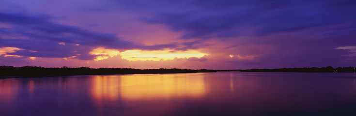 This is the ocean and Pine Island at sunset. There is a pinkish purple cast in the sky that is reflected in the water. The nearby land is in silhouette.