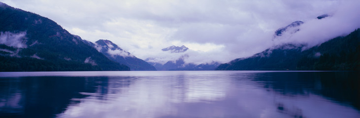 Wall Mural - This is an image of the Olympic Peninsula with Crescent Lake in the foreground. The mountains in the background are covered with low altitude clouds. There is a reflection in the lake of the clouds and mountains. The sky is overcast with clouds.