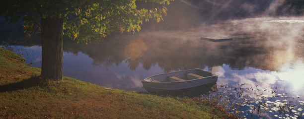 This is a row boat sitting at the edge of a pond in autumn. The pond is near Route 10.