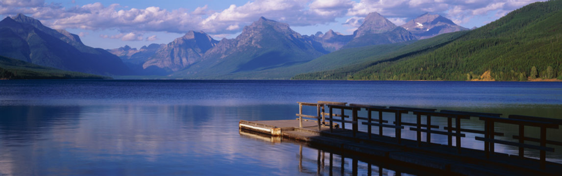 This is a boat dock at Lake McDonald. The blue water of the lake surrounds the dock with mountains in the background.