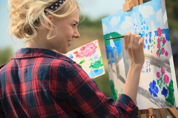 Beautiful blonde woman artist paints a colorful picture.