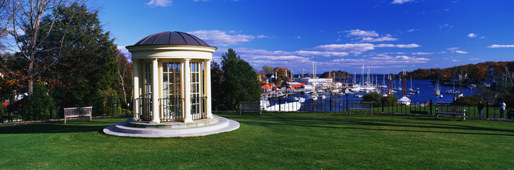 Wall Mural - This is the gazebo of the public library. It has a view of the harbor with autumn foliage surrounding it. It is set on a green lawn and the gazebo has off-white columns, a black wrought iron railing and windows.