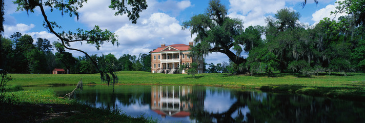 This is a southern plantation called Drayton Hall. It is a pre-Revolutionary plantation set on the Ashley River. It has Georgian Palladian architecture and was built from 1738-1742. It is set back on a green lawn with a pond showing the reflection of the plantation in the water. Wall mural