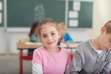 schulkind im klassenzimmer schaut lächelnd in die kamera