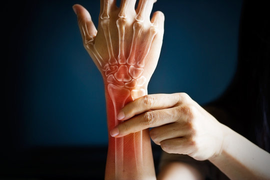 Acute pain in a woman wrist, colored in red on dark blue background