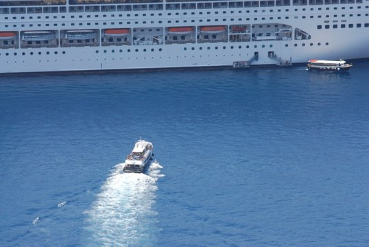 Tender boat is heading to a cruise ship