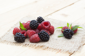 Fresh sweet red raspberry, blueberries and mint on light wooden table, selective focus