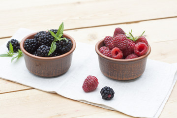 Fresh sweet red raspberry and blueberries in a clay pot and mint on light wooden table, selective focus