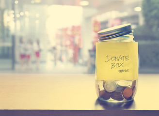 Donate box, coin in the glass bottle, vintage color tone