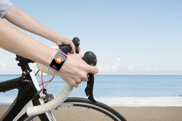 Biking woman hands wearing health sensor smart watch