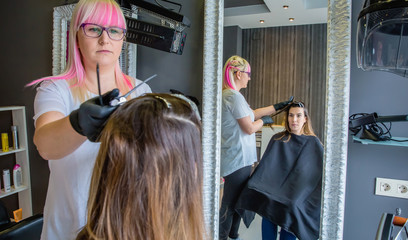 Woman looking in mirror to hairdresser combing hair