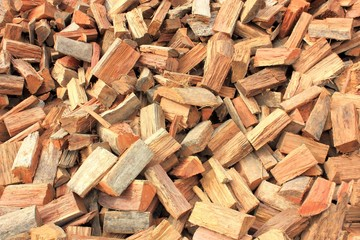 Close up of roughly split firewood heap textured background