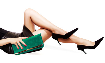 Wall Mural - Beautiful legs woman with black leather skirt laying on the floor. isolated on white. Black high heels and green handbag.