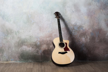 The guitar stands near the wall in the style of grunge, music, musician, hobby, lifestyle, hobby